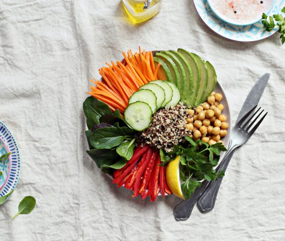 Quinoa salad with fresh vegetables,avocado and chick pea. Detox Buddha bowl with quinoa, spinach and chopped vegetables. Healthy eating and super food concept.Overhead view