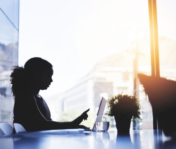 Silhouetted shot of a young businesswoman working on a laptop in an office