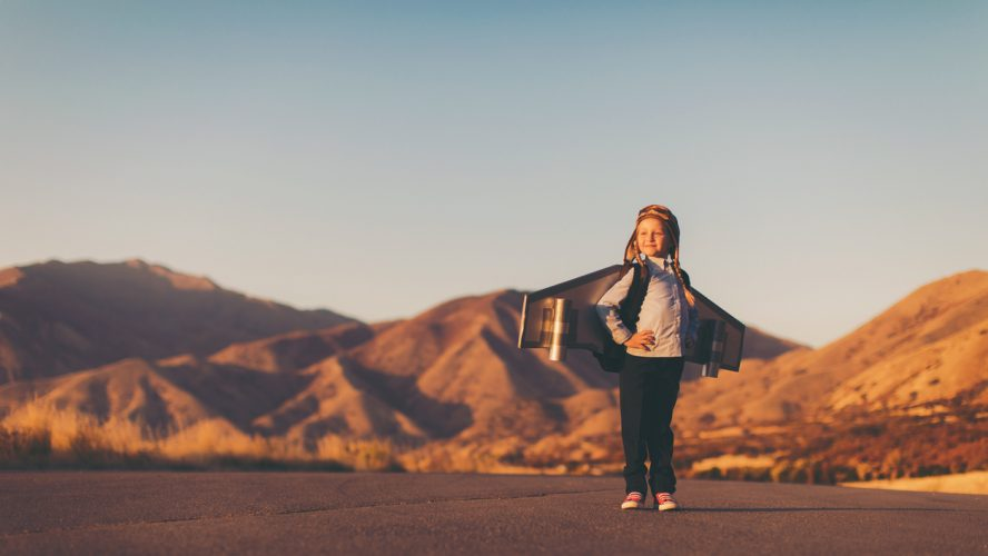 A young girl businesswoman or student dressed in business attire places her hands on her hips while wearing a jet pack and flying cap and goggles. She is standing on a country road among the mountains of Utah, USA. She is confident in her abilities to lead her business and obtain her goals. She can do anything a boy can.