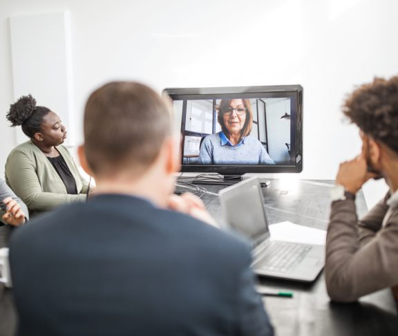 Mature businesswoman communicating with team through video call. Senior female professional seen on computer monitor sharing ideas with colleagues sitting at conference table in office.