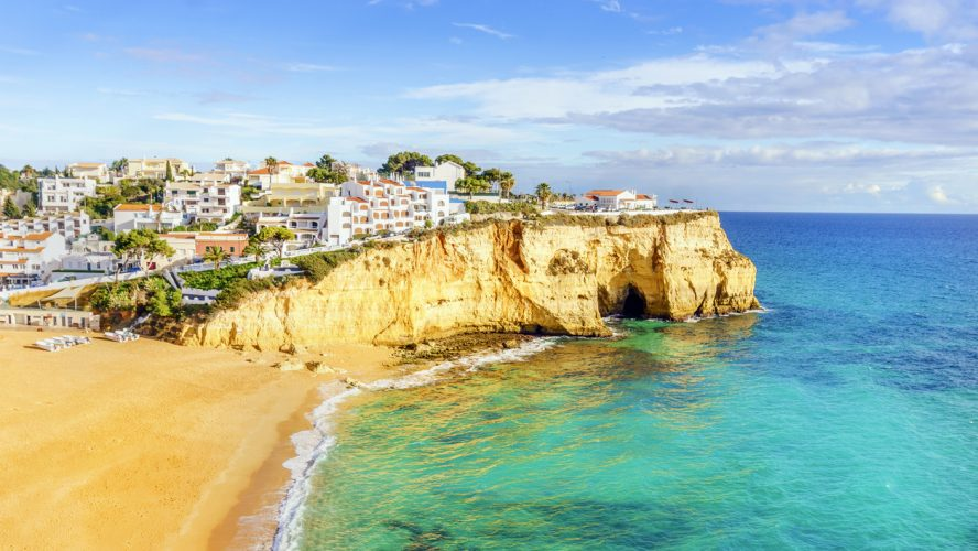 Sandy beach between cliffs in front of charming white architecture of Carvoeiro and turquoise Atlantic Ocean, Algarve, Portugal