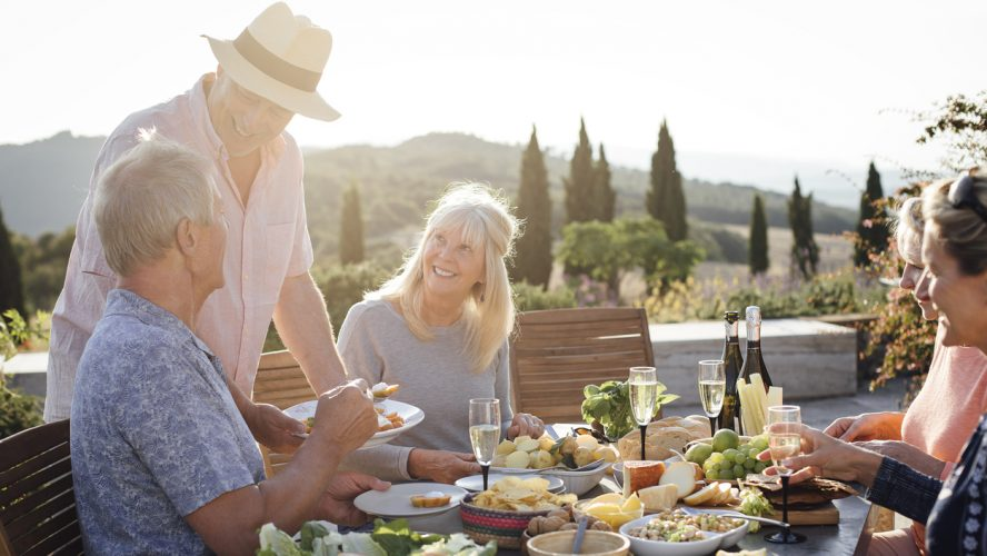 A group of mature friends are sitting around an outdoor dining table, eating and drinking. They are celebrating their holiday with a glass of champagne and enjoying each others company. The image has been taken in Tuscany, Italy.