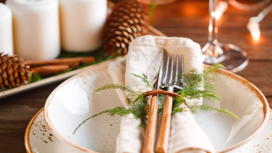 Decorated Thanksgiving or New Year table setting among white candles and winter decor. The concept of a festive dinner.