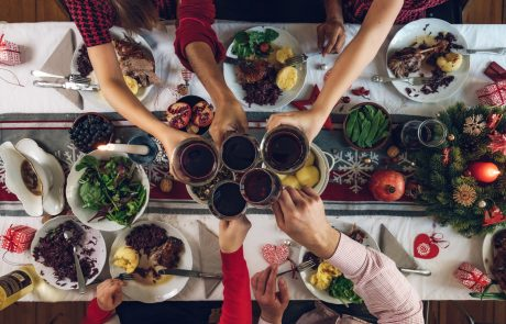 overhead view on family sitting around christmas table with traditional Christmas roast
