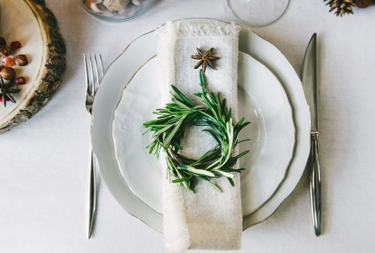 Decorative green wreath on a napkin as a part of table appointments, clean white tablecloth background, top view. Christmas table place setting.