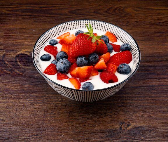 en skål med synede mælkeprodukter. på toppen er der frisk frugt