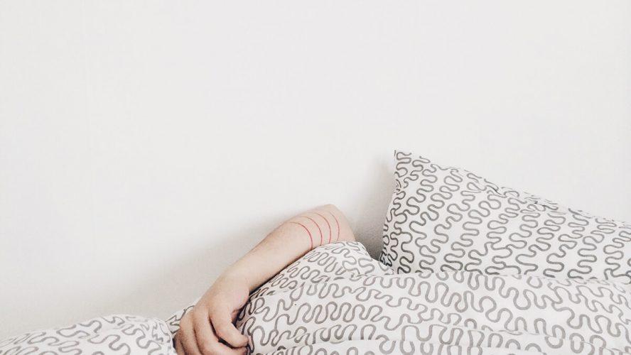 Kvinde ligger under sengen og prøver på at sove