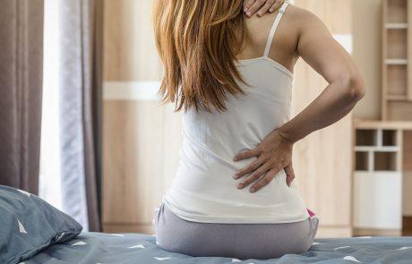 dame sidder på kanten af sengen med kroniske smerter