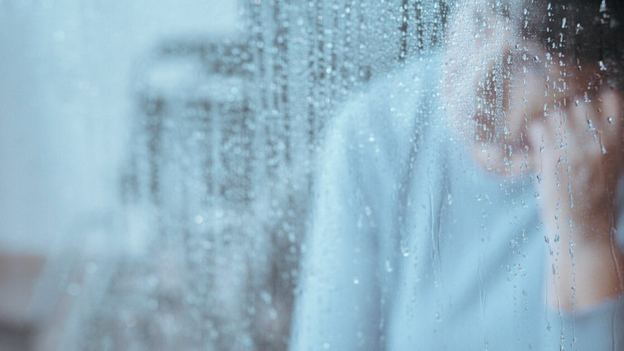 dreng med depression kigger på regnen