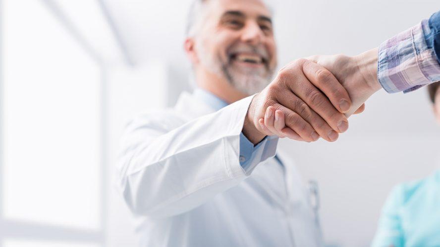 læge trykker patient i hånden