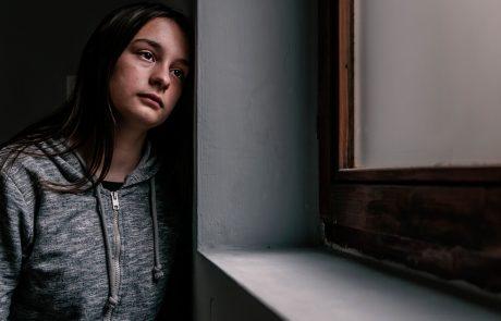 Ung kvinde kigger trist ud af vinduet
