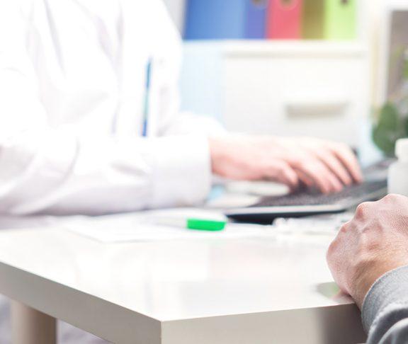 Mand sidder og snakker med en læge