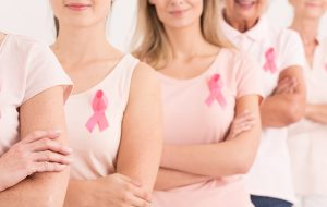 Kvinder står med knæk cancer mærker på trøjen