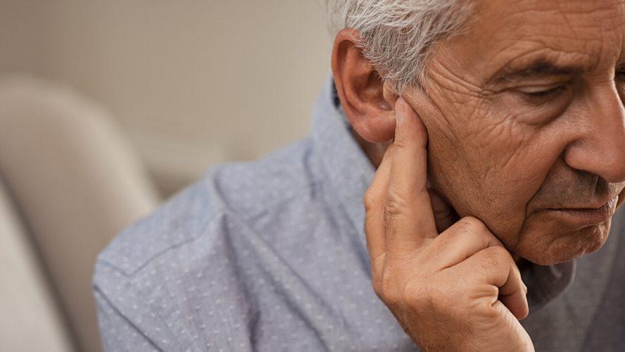 Mand med høretab sidder og lytter