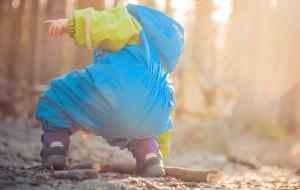 barn iklædt flyverdragt og gummistøvler leger ude i skoven