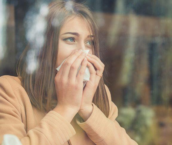 kvinde med allergi eller astma pudser næse