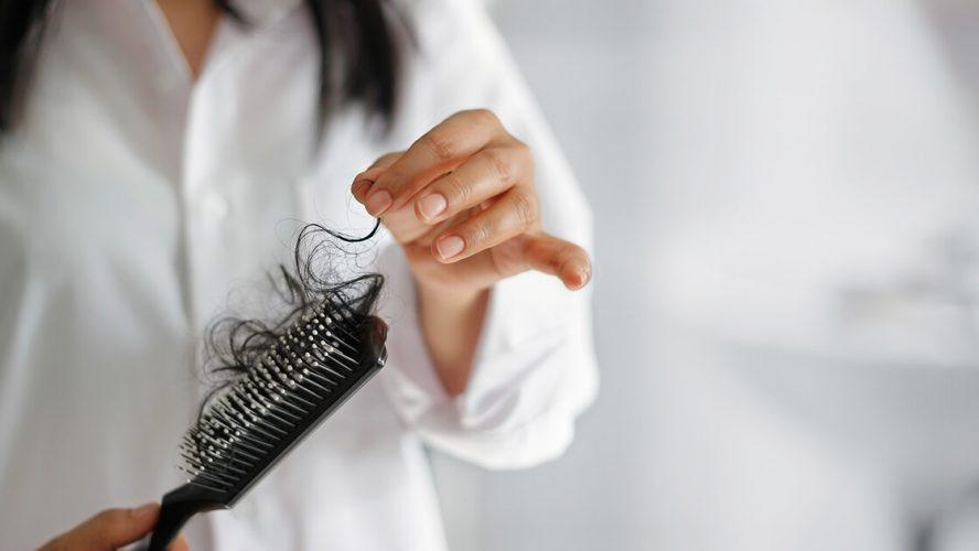 Kvinde med hårbørste fyldt med lange hår