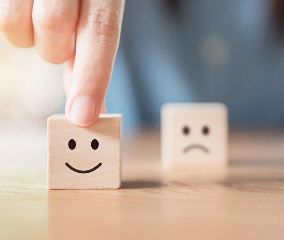 glad og ked af det terninger står på et bord