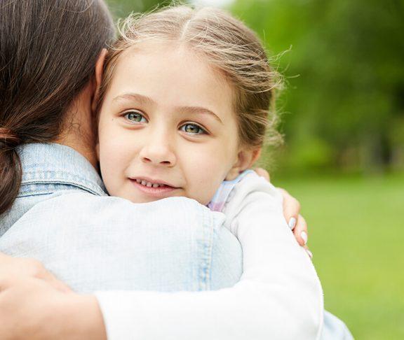 Barn krammer kvinde som hun er i pleje hos