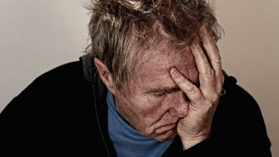 Ældre mand tager sig utilpas til panden