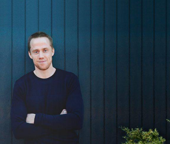 Henrik duer foran blåt stakit