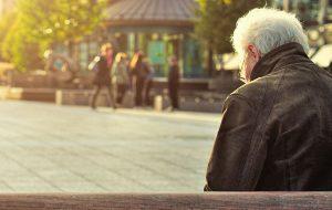 Enlig mand siddende alene på en bænk
