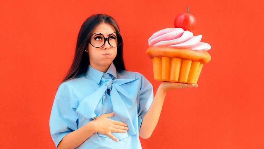 Kvinde holder sig på maven med oversize glutenfyldt cupcake i hånden