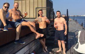 Nikolaj i badebukser drikker øl på bryggen med vennerne