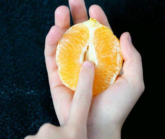 kvinde holder appelsin i hånden, der symboliserer kvindens underliv