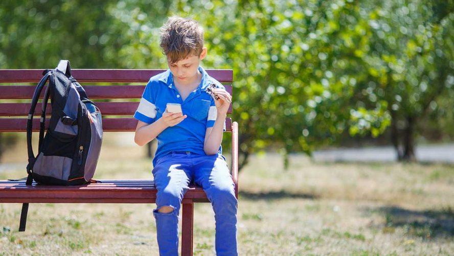 Dreng sidder på en bænk med sin rygsæk og kigger på sin telefon