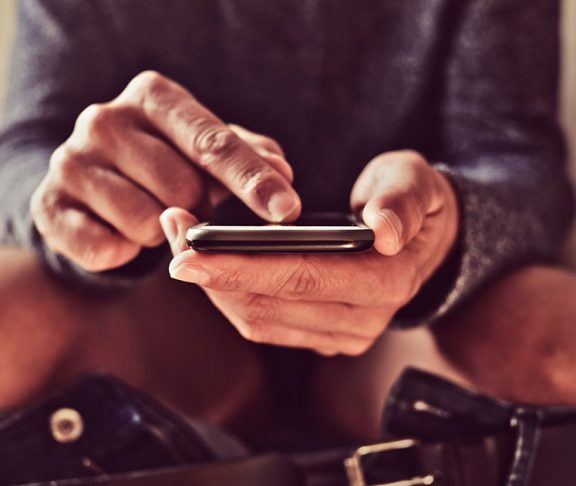 Mand sidder på toilettet og kigger på sin mobil