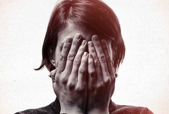 Flov kvinde gemmer sig bag sine hænder