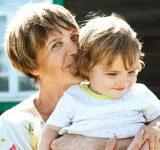Mormor med barnebarn i sommersolen