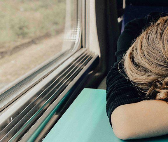 Træt kvinde sover i tog
