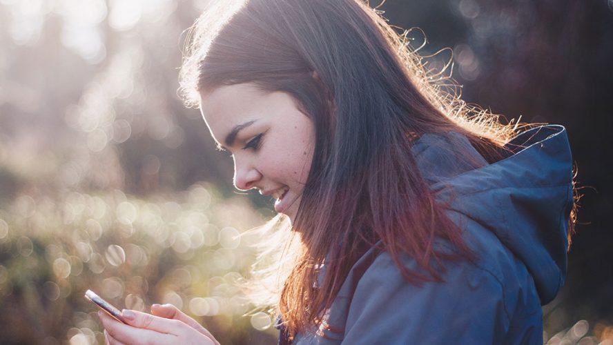 ung pige står med telefon