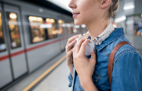 Unrecognizable young woman in denim shirt with earphones, standing at the underground platform, waiting to enter a train