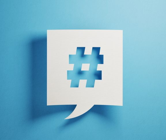 White chat bubble on blue background. There is a hashtag icon on chat bubble. Horizontal composition with copy space.