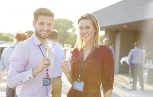 Portrait of smiling young business colleagues standing with wineglasses at rooftop during party