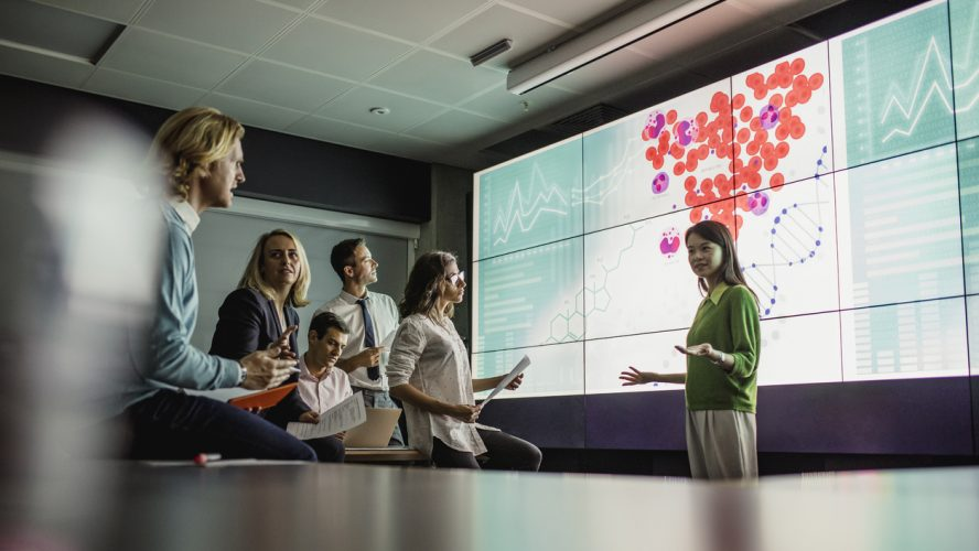 Group of business professionals in a dark room standing in front of a large data display screen with information.