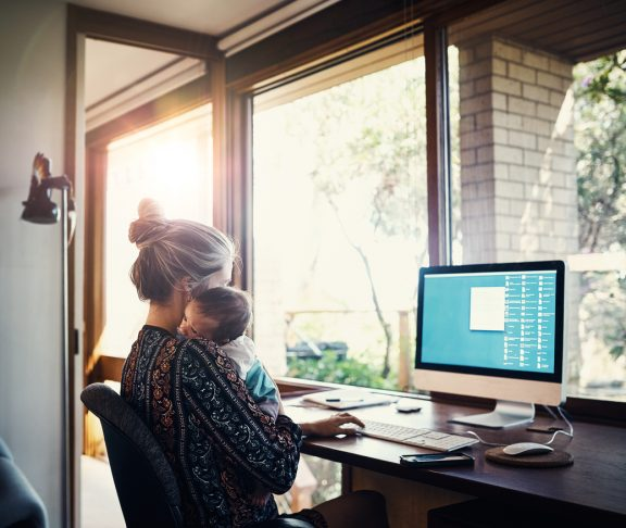 Shot of a young woman working at home while holding her newborn baby son