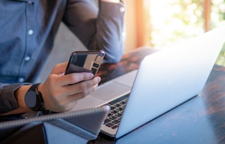 Male hand holding smartphone. Businessman using laptop computer and digital tablet while working in the cafe. Mobile app or internet of things concepts. Modern lifestyle in digital age.