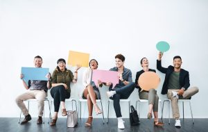 Studio shot of a group of businesspeople holding up speech bubbles while they wait in line
