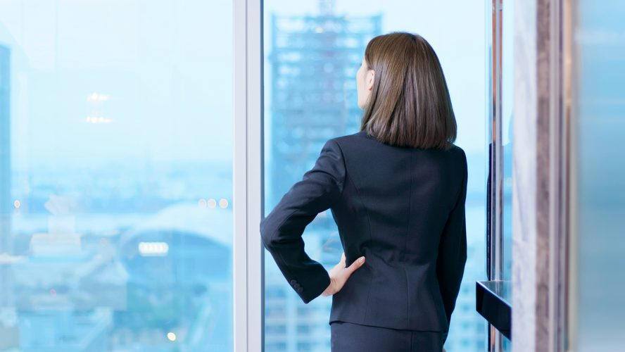 business woman gaze through the window thoughtfully and see outside