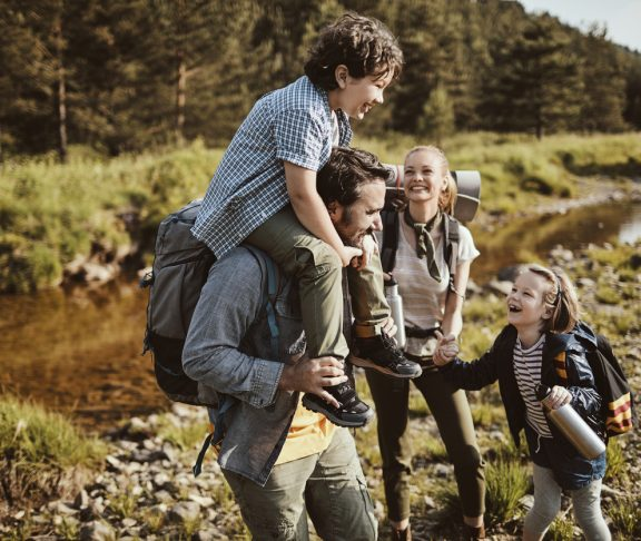 Close up of a young family hiking through the woods