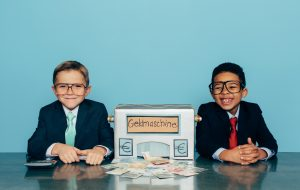 Two young boys and businessmen makes a profit with a Euro making machine. Lots of money comes out of the homemade money machine. Bling. Boys are dressed in business suit with glasses and have large smiles on their face. Retro styled.