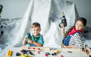 Cute boy and girl playing with toy tools in workshop and smiling at camera
