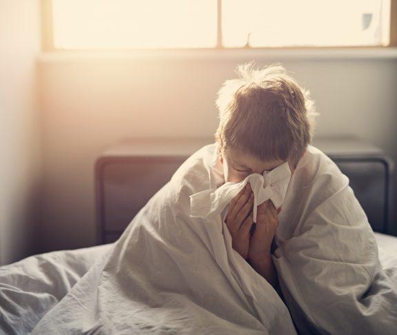 Portrait of sick little boy aged 8 lying in bed.