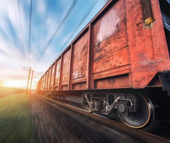 Railway station with cargo wagons and train in motion against sunny sky. Concept industrial landscape at sunset. Railroad. Motion blur effect. Blurred railway platform. Heavy industry. Cargo shipping