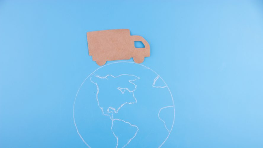 Paper cut of truck on the earth. delivery concept