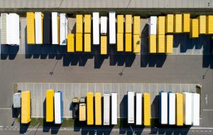 Aerial view of cargo containers, semi trailers, industrial warehouse, storage building and loading docks, Bavaria, Germany